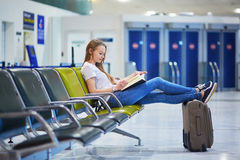 Het mooie jonge toeristenmeisje met rugzak en draagt bagage in internationale luchthaven Royalty-vrije Stock Afbeelding