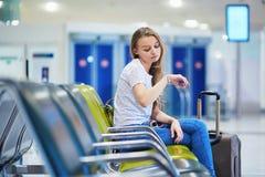 Het mooie jonge toeristenmeisje met rugzak en draagt bagage in internationale luchthaven Stock Foto's