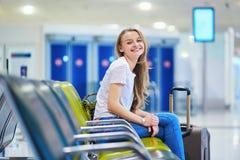 Het mooie jonge toeristenmeisje met rugzak en draagt bagage in internationale luchthaven royalty-vrije stock foto's