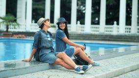 Het mooie jonge toeristenvrouwen genieten die het zitten spreken samen dichtbij de pool in het park stock videobeelden