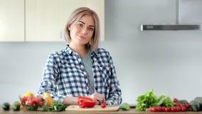 Het mooie jonge toevallige huisvrouw stellen bij keuken tijdens kokend gezond voedsel die camera bekijken stock footage