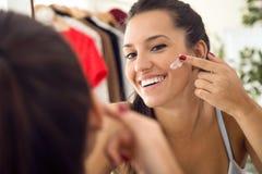 Het mooie jonge vrouw geven van haar huid dichtbij spiegel in de badkamers Stock Foto's