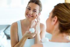 Het mooie jonge vrouw geven van haar huid die zich dichtbij spiegel in de badkamers bevinden Royalty-vrije Stock Fotografie
