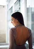 Het mooie jonge vrouw letten op door het venster Stock Foto