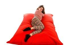 Het mooie jonge vrouw liggen op rode vierkante gevormde beanbag bank is Stock Foto