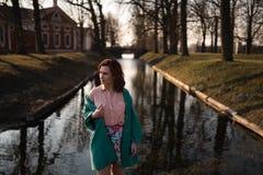Het mooie jonge vrouw ontspannen dichtbij een kanaalrivier in een park dichtbij het paleis in Rundale, Letland, 2019 stock foto's