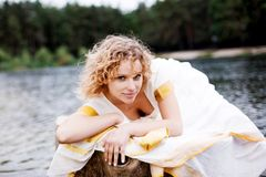 Het mooie jonge vrouw ontspannen dichtbij het meer Royalty-vrije Stock Fotografie
