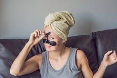 Het mooie jonge vrouw ontspannen met gezichtsmasker thuis Gelukkige blije vrouw die zwart masker op gezicht toepassen royalty-vrije stock afbeelding