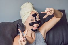 Het mooie jonge vrouw ontspannen met gezichtsmasker thuis Gelukkige blije vrouw die zwart masker op gezicht toepassen stock foto's