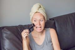 Het mooie jonge vrouw ontspannen met gezichtsmasker thuis Gelukkige blije vrouw die zwart masker op gezicht toepassen stock foto