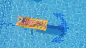 Het mooie jonge vrouw ontspannen op een gele opblaasbare matras in een pool stock video