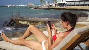 Het mooie jonge vrouw ontspannen sunbed met slimme telefoon stock video