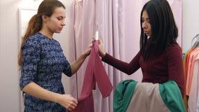 Het mooie jonge vrouw proberen op nieuwe kleding, maar houdt niet van het en kiezend nieuwe  stock video