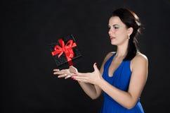 Het mooie jonge vrouw spelen met een zwarte giftdoos Royalty-vrije Stock Afbeeldingen