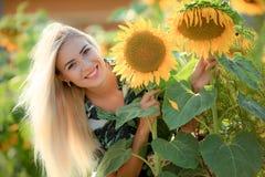 Het mooie jonge vrouw stellen dichtbij zonbloemen de zomerportret bij het gebied Gelukkige vrouw op schoonheidsgebied met zonnebl stock afbeelding