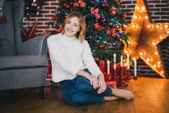 Het mooie jonge vrouw stellen onder Kerstboom Stock Foto