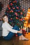 Het mooie jonge vrouw stellen onder Kerstboom Royalty-vrije Stock Afbeeldingen