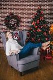 Het mooie jonge vrouw stellen onder Kerstboom Stock Afbeeldingen