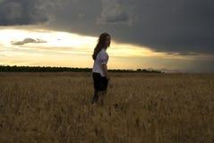 Het mooie jonge vrouw stellen op een tarwegebied bewolkte dag Roodharig tiener royalty-vrije stock afbeeldingen