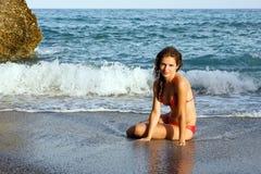 Het mooie jonge vrouw stellen op het strand Stock Foto's