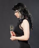 Het mooie jonge vrouw vieren met een glas champagne Royalty-vrije Stock Afbeeldingen
