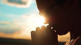 Het mooie jonge vrouwelijke bidden het meisje vouwde haar indient gebedsilhouet bij zonsondergang langzame geanimeerde video Het  stock videobeelden