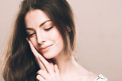 Het mooie jonge vrouwenportret leuke tedere zuivere glimlachen wat betreft haar wang door achtergrond van de palm de aantrekkelij Stock Afbeeldingen