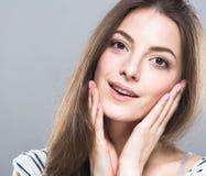 Het mooie jonge vrouwenportret leuke tedere zuivere glimlachen wat betreft haar wangen door vingers aantrekkelijke grijze achterg Stock Foto