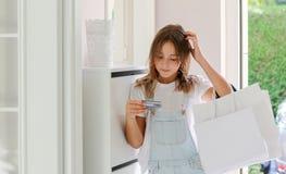 Het mooie jonge weerspiegelende tienermeisje met het winkelen doet het bekijken creditcard in zakken die haar hoofd krassen stock fotografie