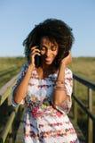 Het mooie jonge zwarte van het afrohaar op cellphonevraag royalty-vrije stock fotografie