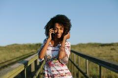 Het mooie jonge zwarte van het afrohaar op cellphonevraag stock afbeeldingen