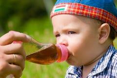 Het mooie jongen drinken van plastic fles Stock Afbeeldingen