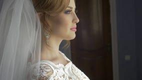 Het mooie kapsel van de het huwelijksmake-up van het Bruidportret, schitterende jonge vrouw in witte kleding thuis reeks stock video
