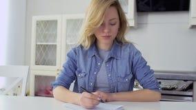Het mooie Kaukasische blonde schrijft een brief aan haar vriend stock video