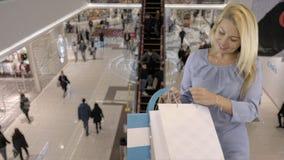 Het mooie Kaukasische blondewijfje die blauwe kleding dragen kijkt in het winkelen zak terwijl status in winkelcentrum met stock footage