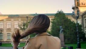 Het mooie Kaukasische brunette is versterkt haar haar en het lopen in profiel dichtbij camera, kijkend recht, zijnd kalm stock video