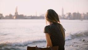 Het mooie Kaukasische meisje in zonnebril zit alleen op stadsstrand, bekijkt terug camera op de verbazende zonsondergang van New  stock footage