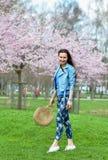Het mooie Mooie Kaukasische Vrouw Bevindende Stellen op de Achtergrond van de Bloeiende Kers van Japan stock foto