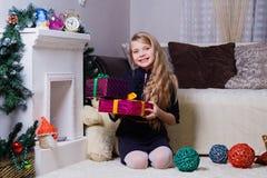 Het mooie Kaukasische wit-haired meisje stellen dichtbij de open haard, Kerstmis en de nieuwe jaarstemming royalty-vrije stock foto's