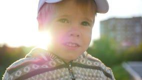 Het mooie kind onderzoekt de camera en glimlacht tegen de achtergrond van zonstralen Pret in openlucht stock videobeelden