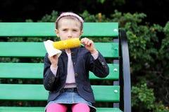 Het mooie kindmeisje eet in openlucht een gekookt graan royalty-vrije stock afbeelding