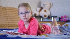 Het mooie kindmeisje spelen met een tabletpc stock videobeelden