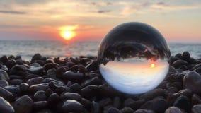 Het mooie landschap als achtergrond binnen kristallen bol legt binnen op strandstenen, zonsondergang en oceaangolven stock videobeelden
