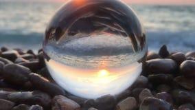 Het mooie landschap als achtergrond binnen kristallen bol legt binnen op strandstenen, zonsondergang en oceaangolven stock footage