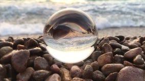 Het mooie landschap als achtergrond binnen kristallen bol legt binnen op strandstenen, zonsondergang en oceaangolven stock video