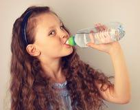 Het mooie lange krullende haarstijl het glimlachen drinkwater van het jong geitjemeisje Royalty-vrije Stock Fotografie