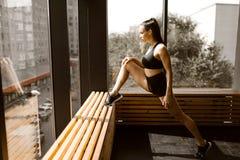 Het mooie lastermeisje gekleed in zwarte sportenbovenkant en borrels doet zich het uitrekken op een houten venstervensterbank in  royalty-vrije stock afbeeldingen