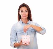 Het mooie Latijnse geld van damebesparingen in een piggybank Stock Afbeeldingen