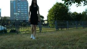 Het mooie magere brunette loopt langzaam op groen gras in de avond stock videobeelden