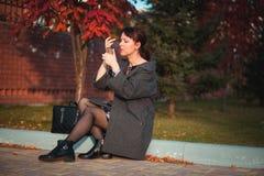 Het mooie maniermeisje schildert lippen in de straat Royalty-vrije Stock Foto's